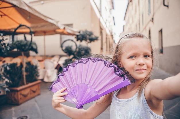 Urocza mody mała dziewczynka outdoors w europejskim mieście