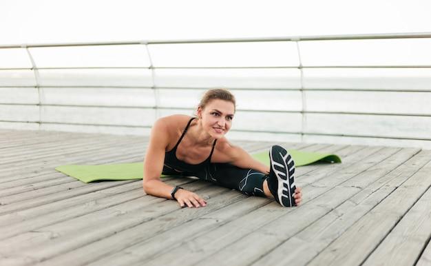 Urocza muskularna sportsmenka w odzieży sportowej robi rozciąganie nóg siedząc w sznurku na tarasie na plaży. sporty na świeżym powietrzu