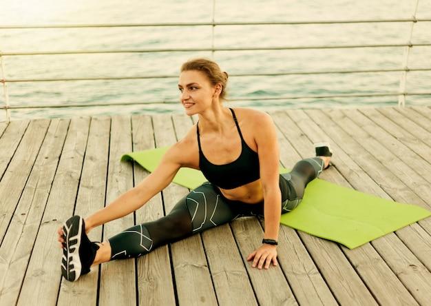 Urocza muskularna sportsmenka w odzieży sportowej robi rozciąganie nóg siedząc w sznurku na tarasie na plaży