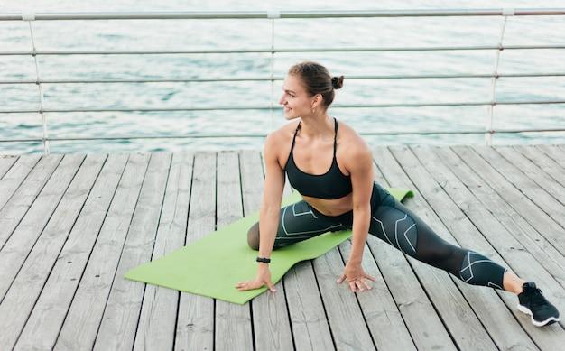 Urocza muskularna sportsmenka występująca w odzieży sportowej, jej ciało robi nogę rozciągającą się na tarasie na plaży. trening na zewnątrz