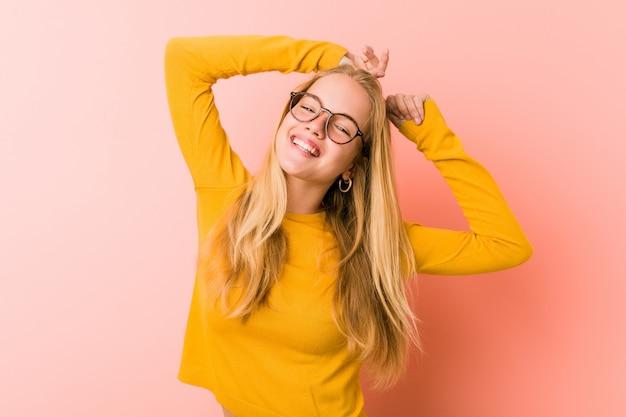 Urocza nastolatek kobiety rozciąganie ręki, zrelaksowana pozycja.