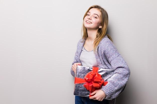 Urocza nastolatka patrząc na pudełko z teraźniejszością na białym tle