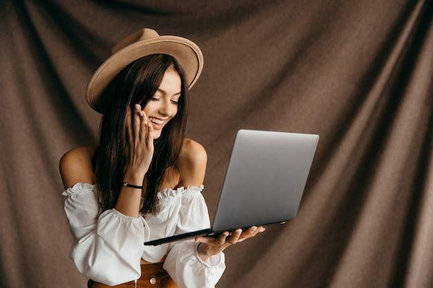 Urocza nastolatka pod wrażeniem zniżki niesamowity cud nowoczesnej technologii gadżet aplikacje blogera na białym tle brązowym