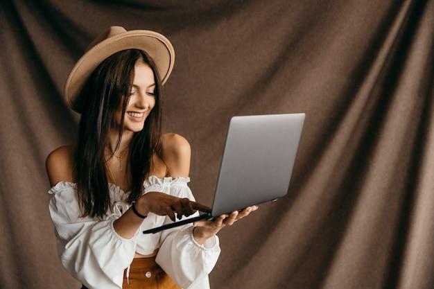 Urocza nastolatka pod wrażeniem zniżki niesamowity cud nowoczesnej technologii gadżet aplikacje blogerka na białym tle brązowym