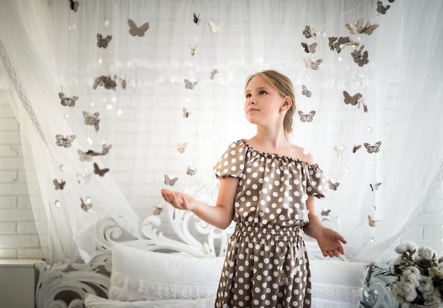 Urocza nastolatka w długiej romantycznej sukience pozuje w przytulnym wnętrzu w girlandę z motyli. pojęcie naiwności i bajki