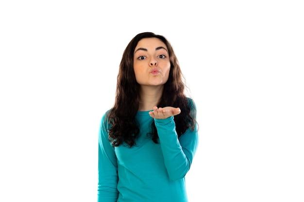 Urocza nastolatka z niebieskim swetrem na białym tle na białej ścianie