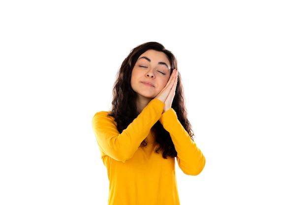 Urocza nastolatka z żółtym swetrem na białym tle na białej ścianie