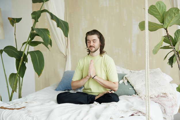 Urocza nauczycielka jogi trzymająca namaste mudrę siedzącą w pozycji lotosu, przystojny medytujący praktykujący medytację w domu siedzący na łóżku w asanie jogi