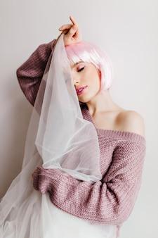 Urocza nieśmiała kobieta w modnych różowych perukach pozująca na jasnej ścianie. spokojna piękna dziewczyna z lśniącymi prostymi włosami, skrywająca twarz za białym obrusem.