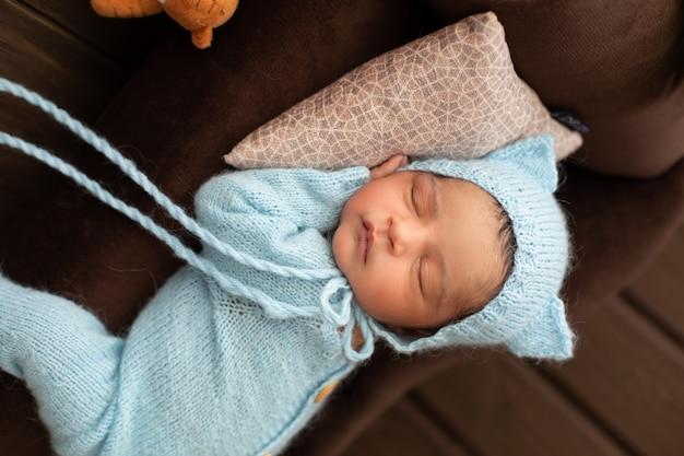 Urocza nowonarodzona śliczna i sympatyczna chłopiec śpi na brązowej kanapie i poduszce w niebieskim szydełkowanym pijamas