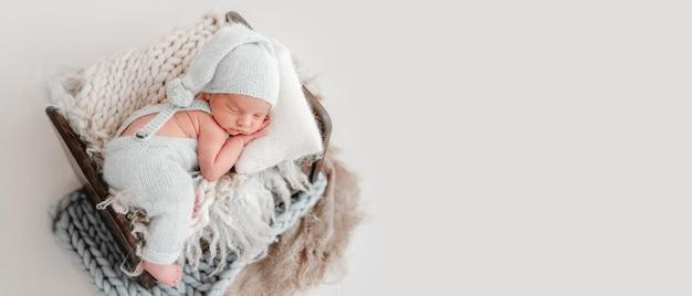 Urocza noworodka dziewczynka na sobie biały strój, leżąc w łóżku w domu ze światłem dziennym i patrząc wstecz. portret uroczego niemowlęcia pod kocem