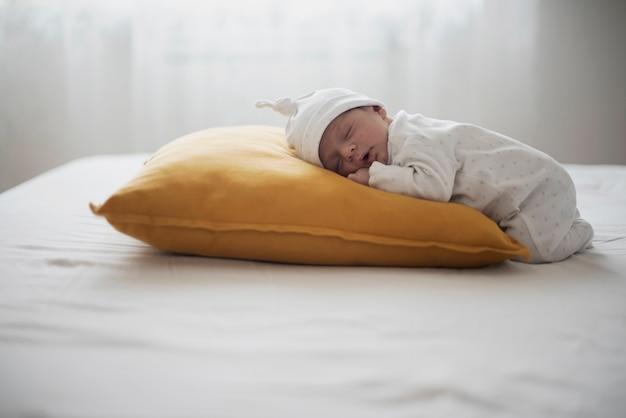 Urocza noworodka śpiąca na żółtej poduszce