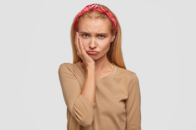 Urocza obrażona piękna młoda kobieta trzyma rękę na policzku, nosi czerwony bandaż na głowie i swobodny sweter, wygląda z ponurym wyrazem