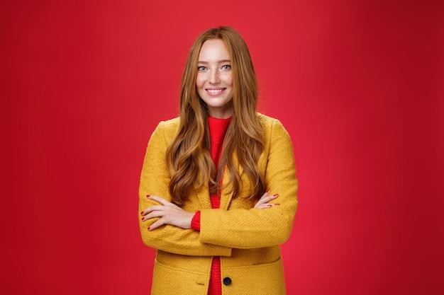 Urocza, odnosząca sukcesy młoda kobieta w żółtym jesiennym płaszczu uśmiechnięta szeroko trzymająca się za ręce skrzyżowane na ciele w pewnej pozie, stojąca zachwycona i szczęśliwa na czerwonym tle.