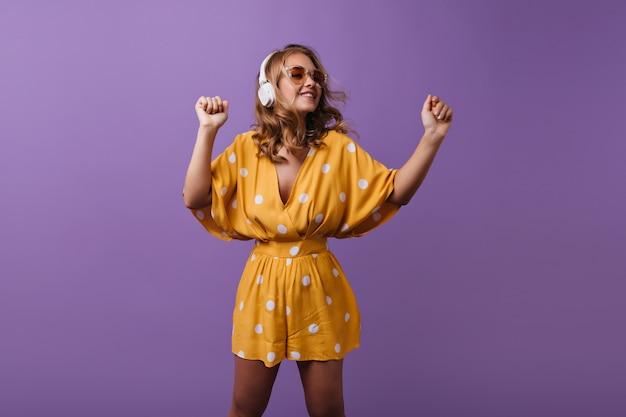 Urocza opalona dziewczyna w białych słuchawkach tańczy na fioletowo. kryty portret eleganckiej blond modelki w żółtym stroju słuchania muzyki.
