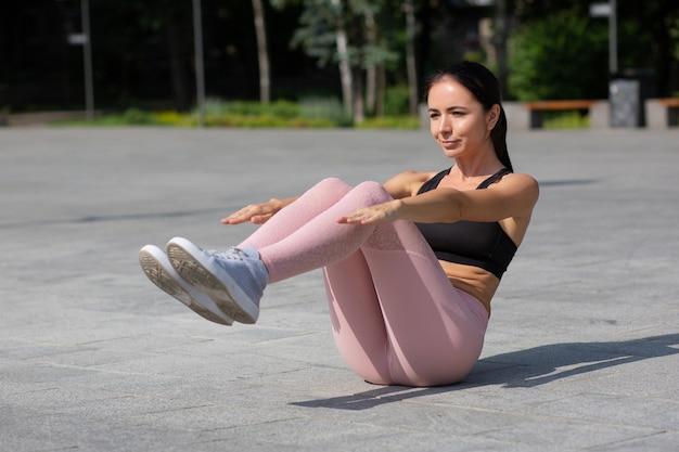 Urocza opalona sportowa dziewczyna w strojach sportowych robi brzuszki w parku