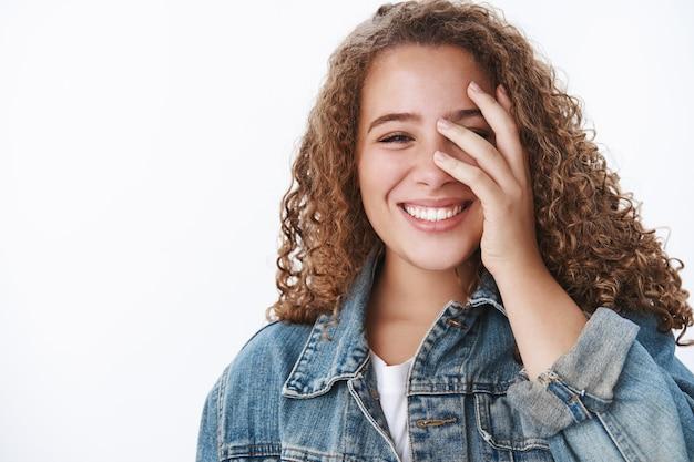 Urocza optymistyczna rozmarzona kręcona pulchna dziewczyna uśmiechnięta białe zęby zarumieniona zalotnie ukryta pół twarzy dłoń baw się dobrze śmieje się urocza ściana studia