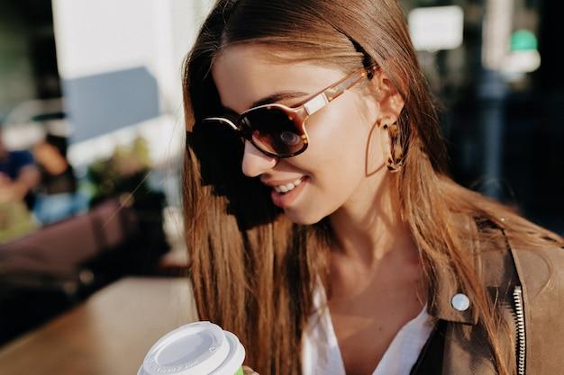 Urocza pani o ciemnych włosach w okularach przeciwsłonecznych pije kawę na drewnianym tarasie ze złotymi liśćmi na tle. zewnątrz portret pięknej białej modelki w mieście