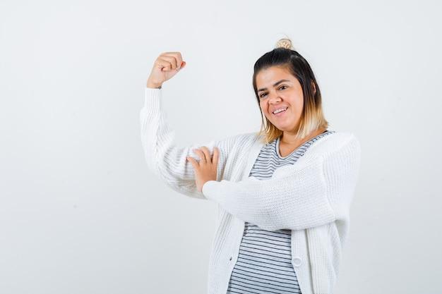 Urocza pani pokazująca mięśnie ramion w t-shircie, sweterku i wyglądająca na zadowoloną. przedni widok.