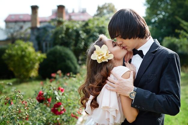 Urocza panna młoda i pan młody stojący blisko siebie na tle parku, zdjęcie ślubne, piękna para, dzień ślubu, portret z bliska, całowanie.