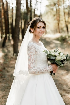 Urocza panna młoda z bukietem w dłoniach na zewnątrz. panna młoda z siwymi włosami w lesie. portret panny młodej. stylowa suknia ślubna. dziewczyna w dniu ślubu.