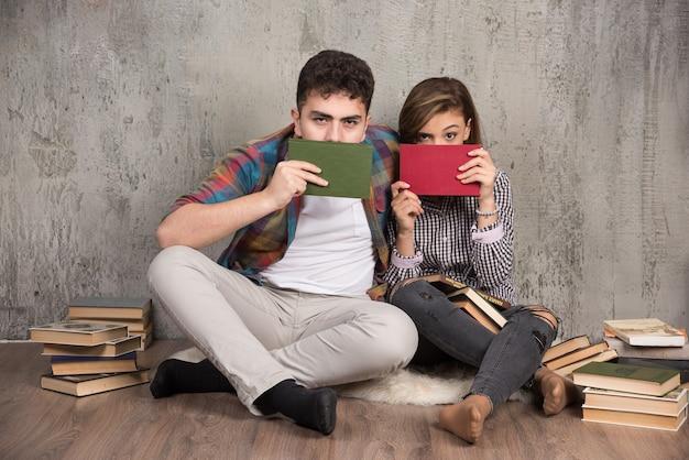 Urocza para chowająca się za książkami i patrząc z przodu
