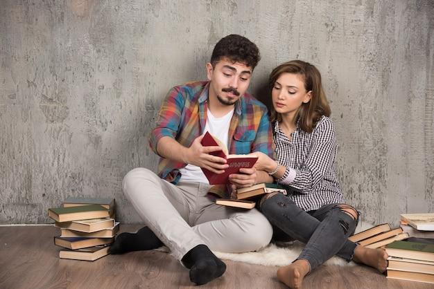 Urocza para czytająca ciekawą książkę siedząc na podłodze