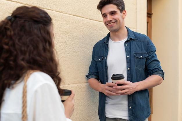 Urocza para delektująca się filiżanką kawy na świeżym powietrzu