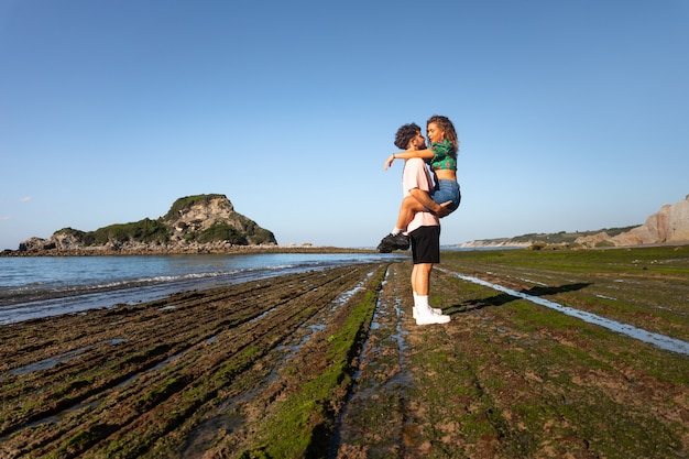 Urocza para heteroseksualna na kamienistej plaży, obejmując się i całując w kraju basków.