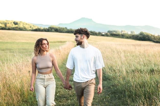 Urocza para heteroseksualna spacerująca i całująca się na trawie