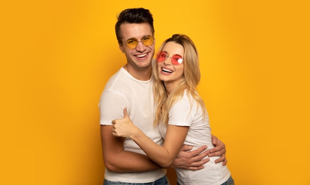 Urocza para hipsterów w wielokolorowych okularach przeciwsłonecznych przytula się i śmieje, podczas gdy dziewczyna pokazuje kciuki w górę