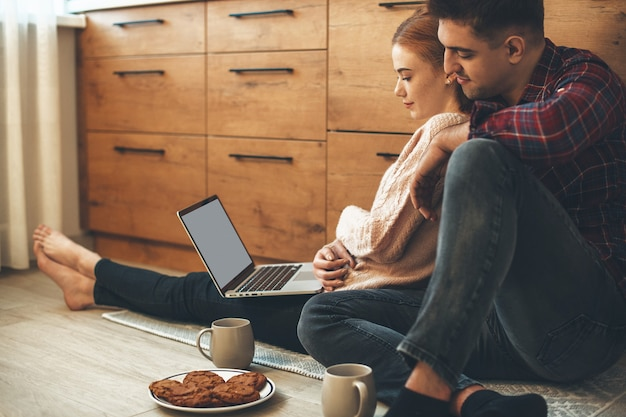 Urocza para kaukaski jedząc śniadanie w kuchni na podłodze, patrząc na komputer
