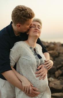 Urocza para kaukaski: mężczyzna przytula i całuje swoją ciężarną żonę nad morzem na zachód słońca. zdjęcie wysokiej jakości