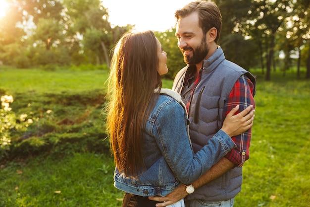 Urocza para mężczyzna i kobieta ubrani w codzienny strój przytulający się i patrzący na siebie podczas wspólnego spaceru po zielonym parku