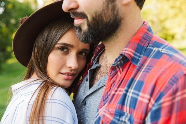 Urocza para mężczyzna i kobieta ubrani w codzienny strój przytulający się razem podczas spaceru po zielonym parku