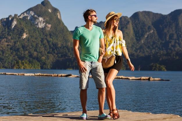 Urocza para pozuje razem na molo przed niesamowitym widokiem na góry, podróżniczy nastrój, stylowe letnie ubrania i dodatki. park narodowy khao sok thailand.