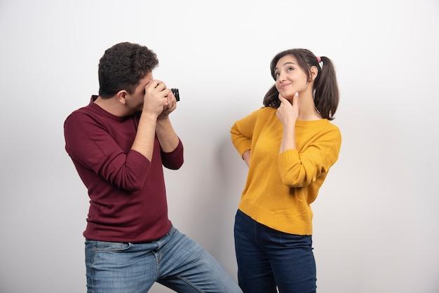 Urocza para robi zdjęcia aparatem i pozuje nad białą ścianą.
