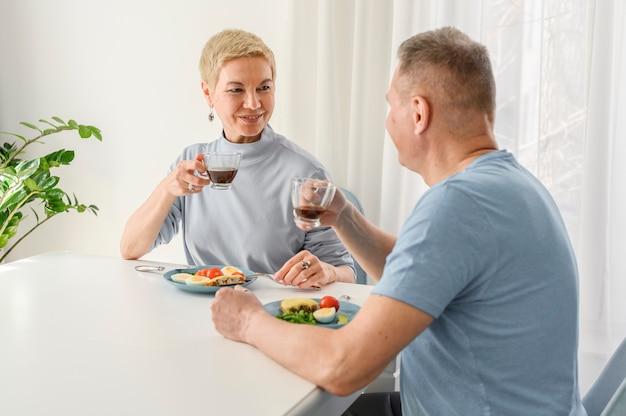 Urocza para seniorów lubi razem jeść zdrową kolację, patrząc na siebie romantycznie drinki