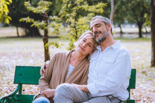 Urocza para seniorów obejmuje razem siedzi na ławce w parku. senoir emerytura relaksuje