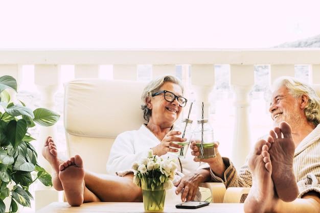 Urocza para seniorów w kurorcie lub zabiegach kosmetycznych w domu lub w hotelu, którzy wspólnie piją koktajl i brzdąkają