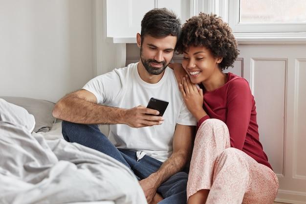 Urocza para siedzi na podłodze obok łóżka i cieszy się domową atmosferą