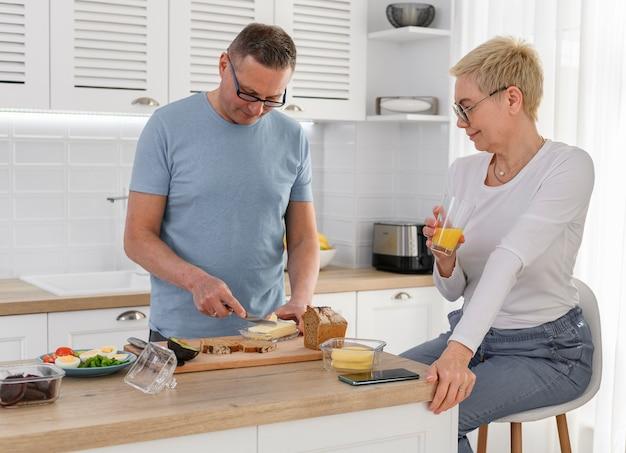 Urocza para starszych gotowania w kuchni kobieta patrząc na męża, jak on gotuje kanapkę dojrzałe