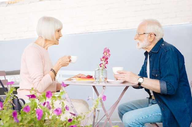 Urocza para starszych siedzi w kawiarni i zachwycającą kawę