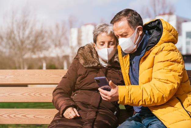 Urocza para starszych w maskach medycznych przy użyciu smartfona siedząc na ławce w parku