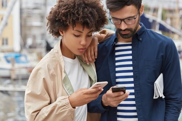 Urocza para stoi obok siebie na niewyraźnym tle zewnątrz, trzyma nowoczesny telefon komórkowy