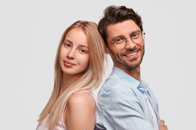 Urocza para stoją plecami do siebie, będąc w dobrym nastroju, odizolowani na białej ścianie. śliczna blondynka, nieogolony, wesoły mężczyzna w okularach jako partnerzy, czuje wsparcie, jest gotowa do pomocy