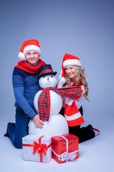Urocza para świąteczna w czapkach świętego mikołaja siedząca z prezentami i bałwanem na niebieskim tle