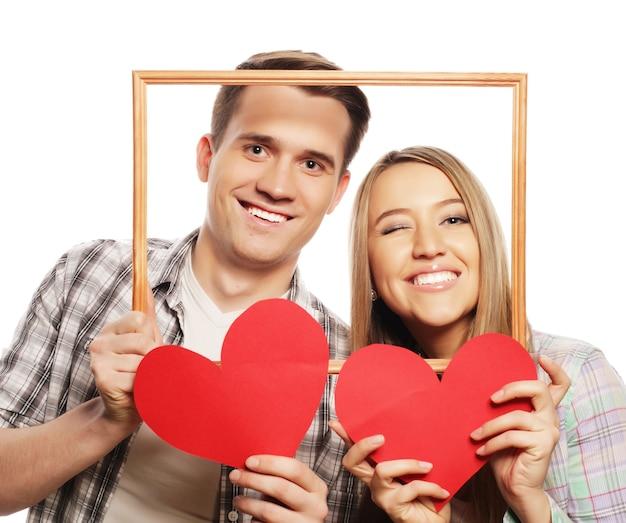 Urocza para trzymając rama i czerwone serca na białym tle.