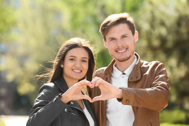 Urocza para trzymająca się za ręce w kształcie serca na zewnątrz