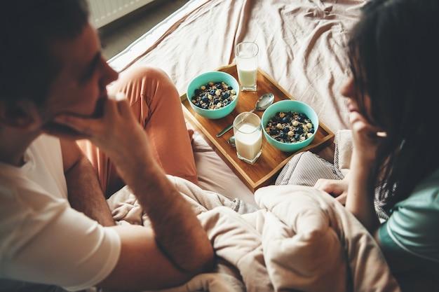 Urocza para w łóżku patrząc na siebie przed jedzeniem płatków śniadaniowych z mlekiem rano